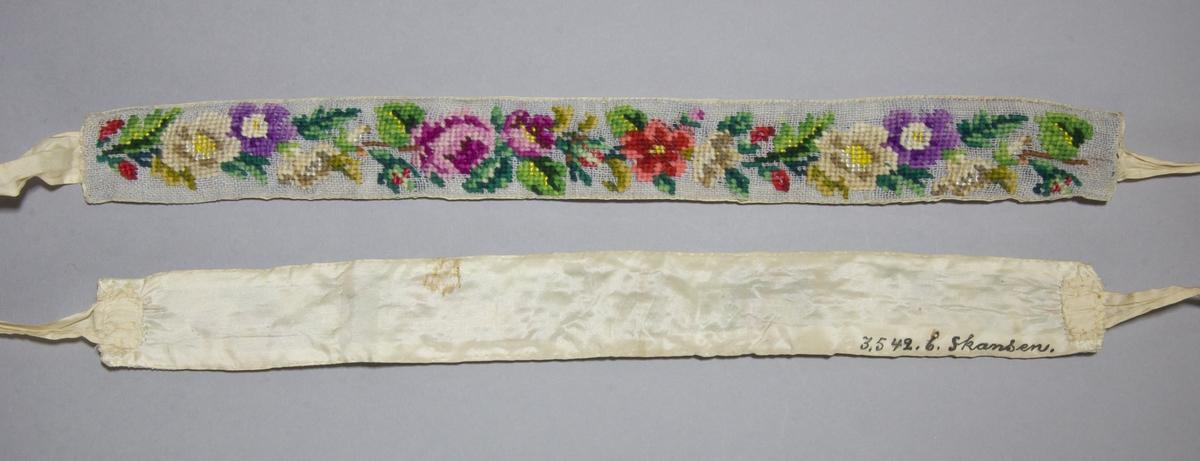Strumpeband för dam, ett par med rosenmönster, korsstygn av ullgarn på stramalj. Vissa detaljer sydda i silke. Baksida av sidentaft, vita sidenband fastsydda på kortsidorna.