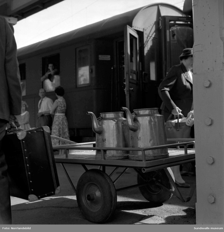 Aktivitet och folkliv på perrongen i Ånge. Stora kaffepannor lastas ombord, en pojke äter korv med bröd.