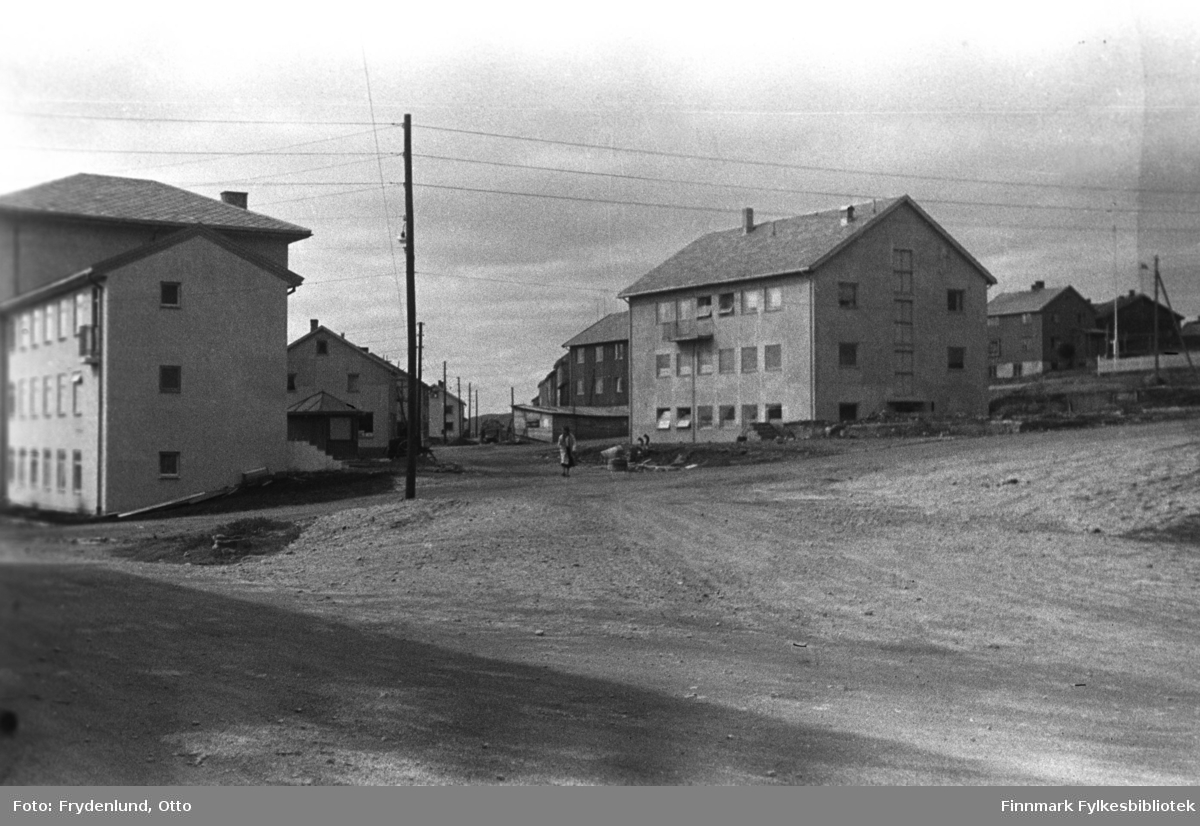 Havnegata fotografert vestover fra sentrum. Nærmest kamera har vi Vadsø rådhus til venstre, og Vadsø sparebank til høyre. Lenger vestover ser vi forretningene Ekviperingen og Saxi