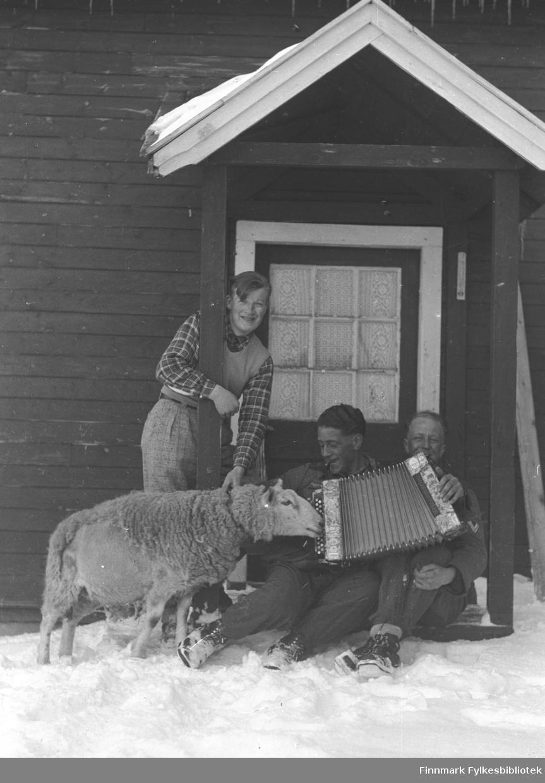 Musikkinteressert vær på gården Mikkelsnes i Neiden. Andreas Mikkola står, mens to ukjente menn (mulig soldater fra Østerike), sitter på trappa med et trekkspill.