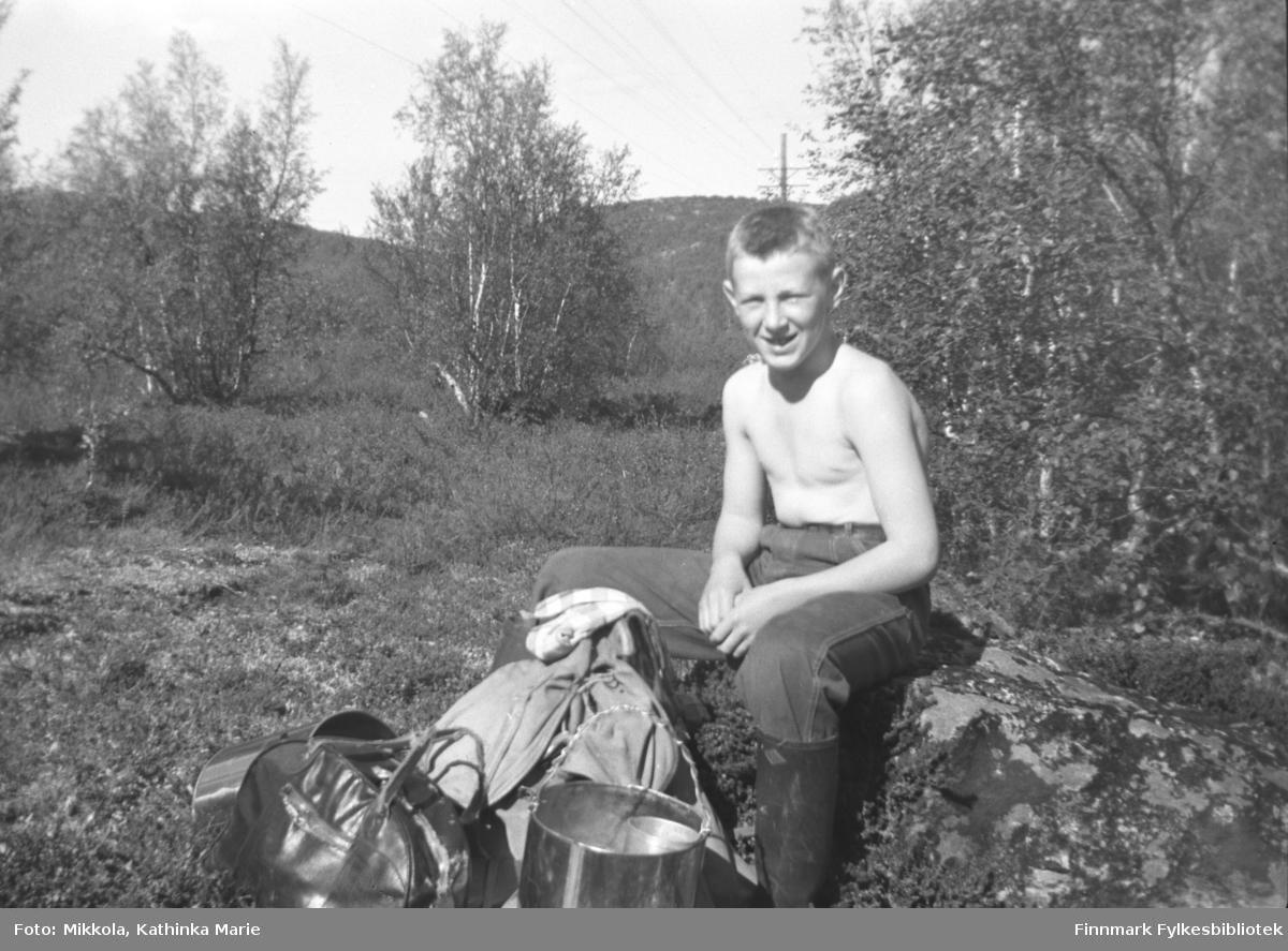 Willy Olsen på bærtur i Neiden-distriktet. Han sitter med bar overkropp på en stein og smiler mot fotografen, og foran ham ser vi ryggsekk og bærspann