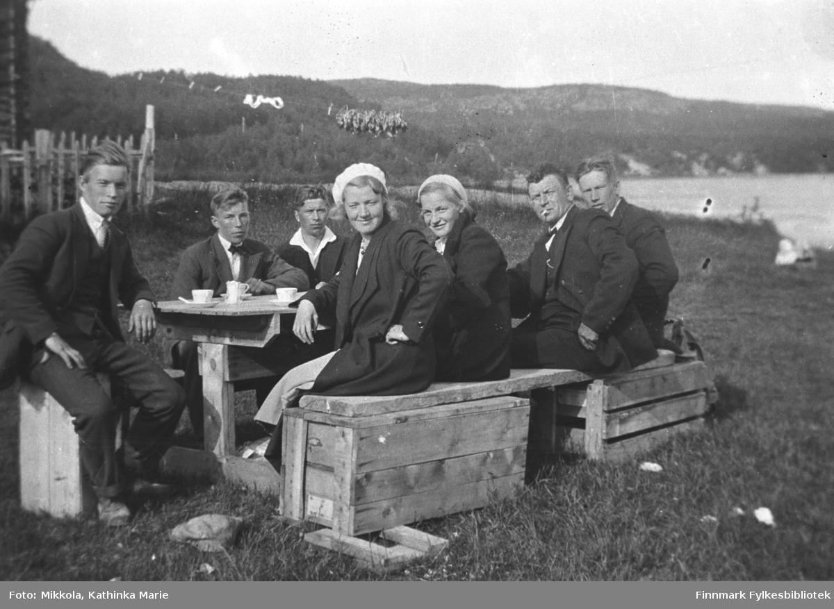 Kaffebord dekket ute ved 'gamlestua' til familien Mikkola i Neiden. En gruppe mennesker sitter på trekasser og enkle benker laget av kasser og trebord lagt over kassene. Fra venstre: Eilif og Frans Labahå, Petter Enbusk, Synnøve og Frida Mikkola, Karl Hallonen. Den siste personen er ukjent