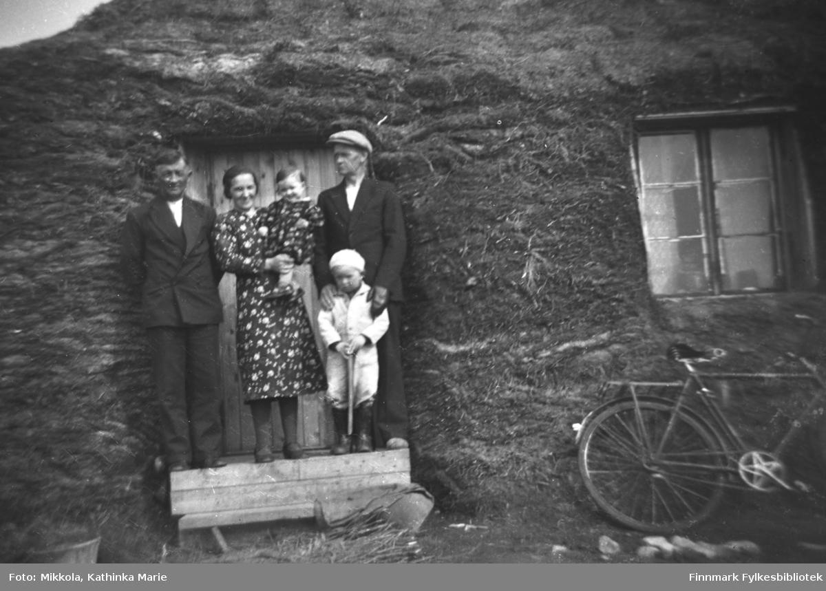 Aleksander og Lembi Dørmænen med datteren Kari på armen foran familiens boliggamme i Neiden. Mannen til høyre er Olaf Jakobsen med sønnen Erik.