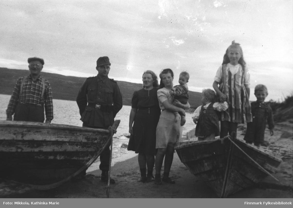 I fjæra på Mikkelsnes. Bildet må være tatt 1943 eller 1944. Fra venstre: Aksel Konrad Mikkola, en østerisk soldat, Synnøve Olsen (født Mikkola) og en dame med barn i fanget (?). Barna på bildet er: Willy, Grete Lill og Per Olsen, barna til Synnøve og Per Sivile Olsen.