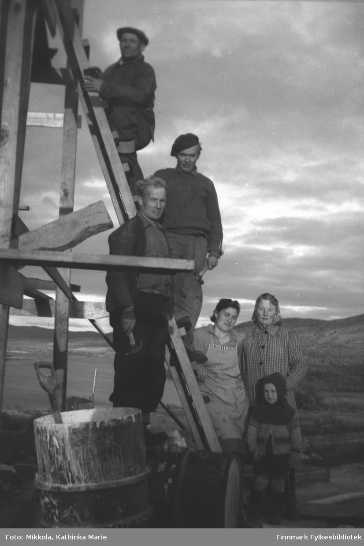 Huset til familien Mathisen ble bygget i 1946, ved Munkelv bru. Mannen øverst i stigen er Per Mathisen. De andre er fra venstre: Frans Aksel Labahå med hammer, så Trygve Mathisen, Ella Mathisen, Mildrid Jerijærvi (gift Abrahamsen). Den lille jenta foran er ukjent.