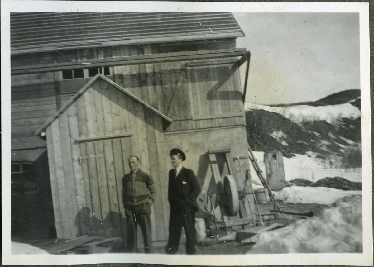 To menn står foran fjøset til skiferbruddet i Friarfjord. Mannen til høyre er Jakob Reeberg (maskinist og smed) og den andre mannen er Sigurd Bjørgum (skiferarbeider). Jakob er kledd i lue, jakke, vest, bukse og slips. Sigurd er kledd i en strikked jakke med mønster på. Begge menn arbeidet på skiferbruddet. Bak mennene kan man se en slipestein og et utedo. Man kan se snø på bakken. Bilde tatt under gjenreisinga etter 2. verdens krig.