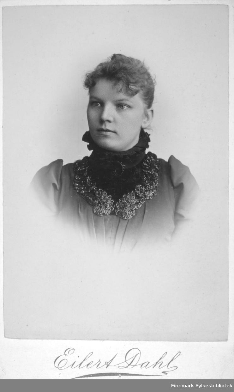 Portrett av en kvinne i mørk bluse med rysjer. Hun har en mørkere løskrage med høy hals. Portrettet er tatt hos Eilert Dahl i Molde.