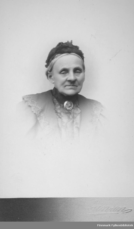 Portrett av en godt voksen dame. Hun har et smykke i halsen og en mørk hatt på hodet.