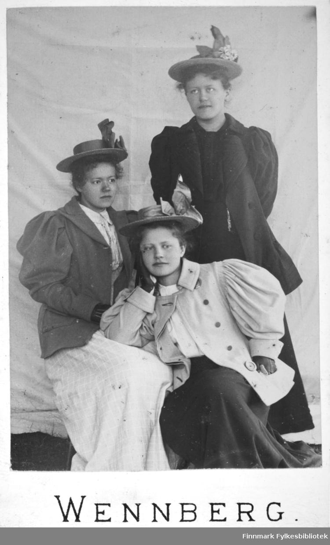 Portrett av tre kvinner iført hatter med pynt på bremen. Hun som står bakerst har en mørk kjole. Hun som sitter til venstre på bildet har en lys kjole og en mørk jakke over. Hun som sitter i midten på bildet har en mørk kjole, hvit bluse og en lys jakke. Hun hviler hodet i høyrearmen og har albuen i fanget på kvinnen ved siden av seg.