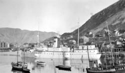 En blikkstille Honningsvåg havn med mange båter. En fiskeskø