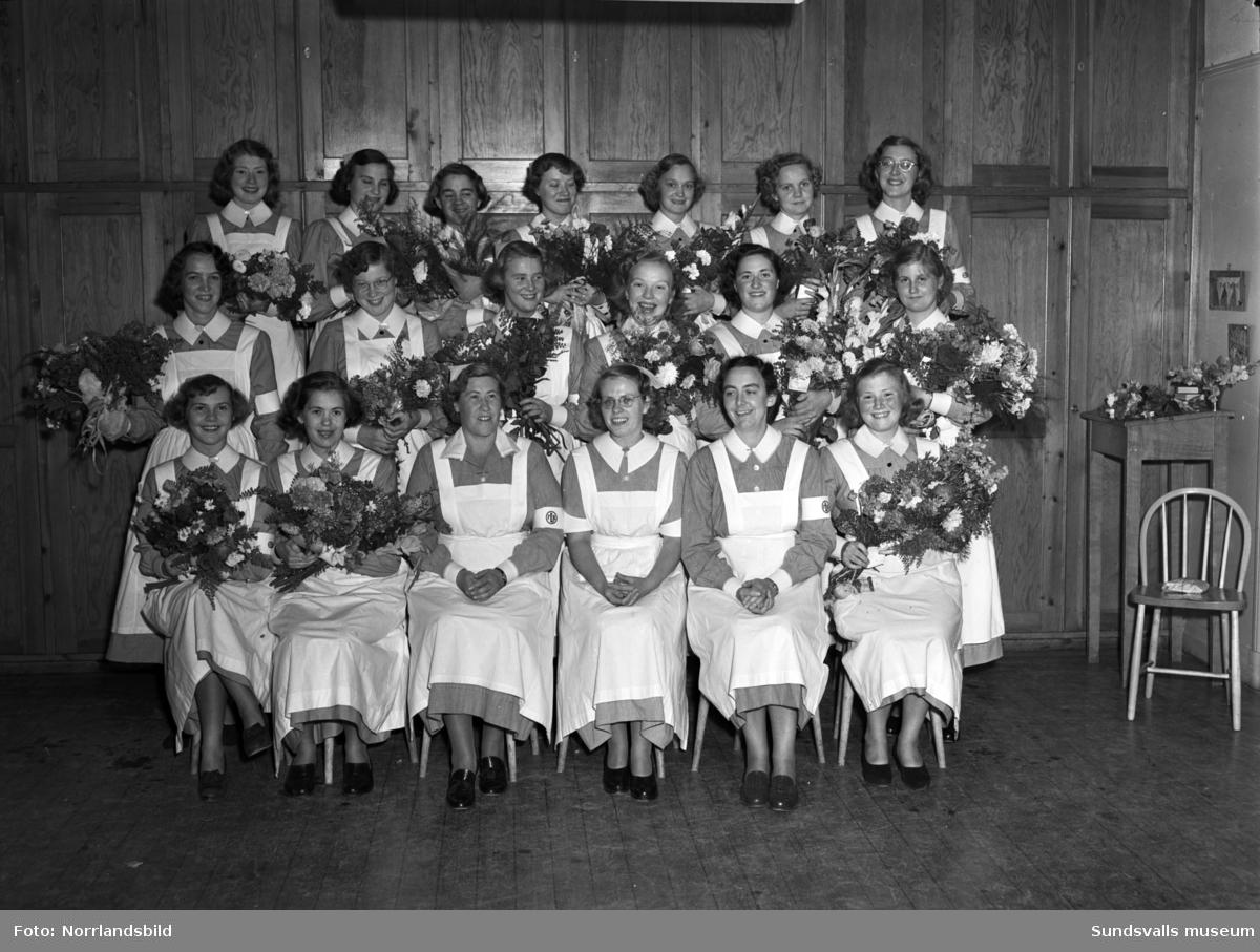Vita Bandets barnsköterske- och husmodersskola. Examensavslutning. På bild 1 ses barnavårdslärarna Elsa Rutbäck (3:e fr vänster nedre raden) samt Anna Lilja (5:e fr vänster nedre raden). Kvinnan i mitten är okänd. På bild 2 ses Elsa Rutbäck krama om en elev.