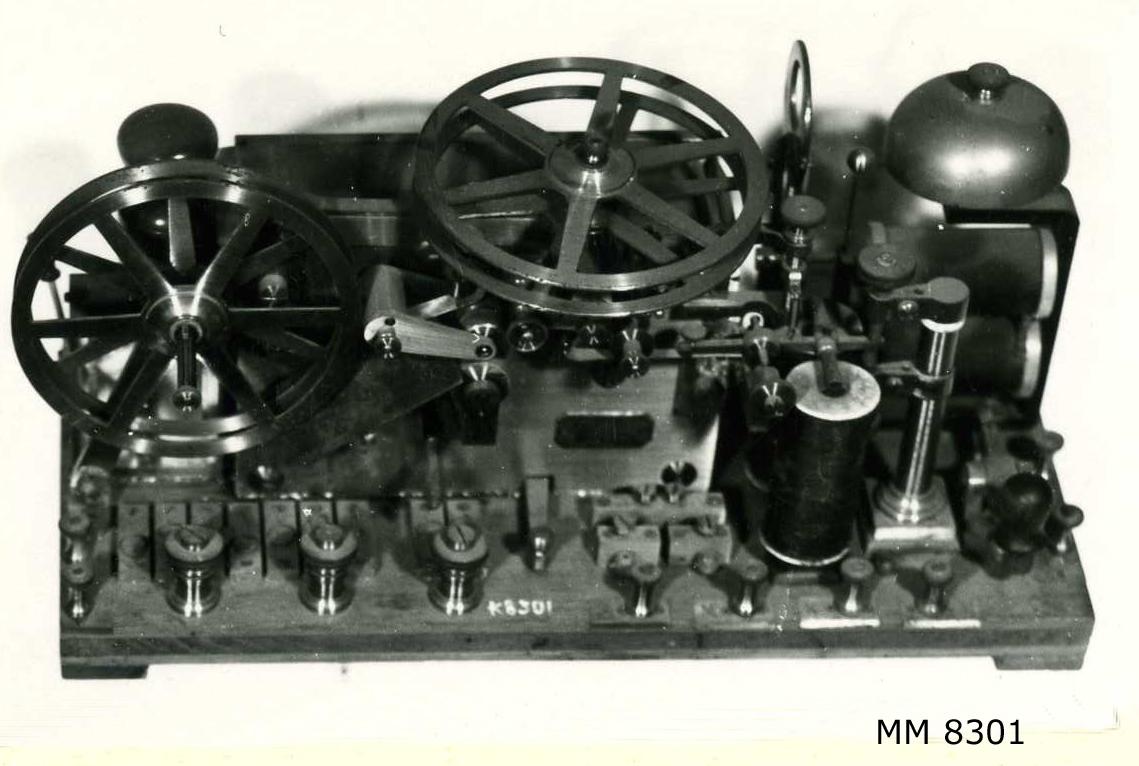 Telegrafapparat av metall på platta av mahogny.