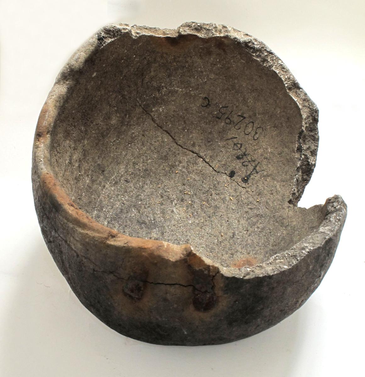 Oval bolle av kleberstein, ornert med 3 horisontale linjebunter under randen. Rester av hankefeste på den ene siden. Dette består av 2 smale skråttstilte jernbånd, nederst festet med en nagle. Rustspor etter hanken på den ene siden av randen. Den ene halvdel av karet temmelig mangelfullt bevart.