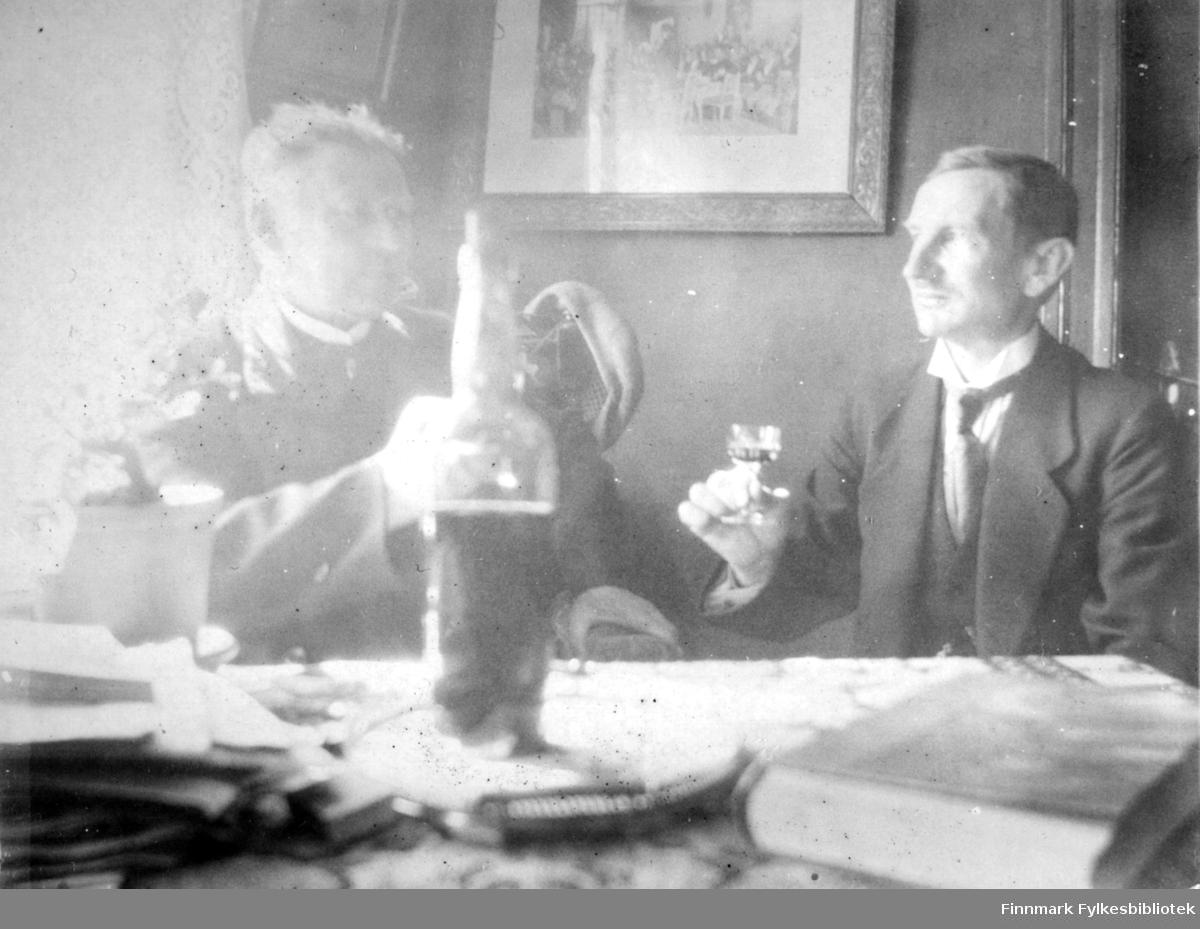 To menn i mørke dresser med hvite skjorter og slips utbringer en skål. En flaske står på bordet og i hendene har de et lite glass hver. På bordet, som har en stor, mønstret duk, ligger en del papirer og en bok. Til venstre skinner solen gjennom et vindu. På veggen bak dem henger et bilde/maleri og helt til høyre ses en liten del av en dør(åpning). På stolryggen bak mannen til venstre henger en lue.