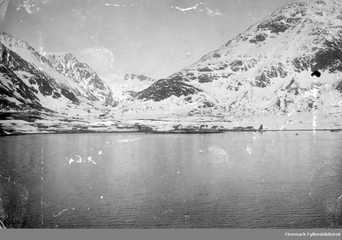 Bergsfjord fotografert fra sjøen en blikkstille og klar vinterdag eller tidlig vårdag. Fjellet Kollaren til høyre på bildet og Gullmundstinden til venstre. Fjellet mellom de to er Tverrfjellet med Svartfjelljøkelen øverst. Bebyggelsen ses i strandkanten og det er endel snø i terrenget.