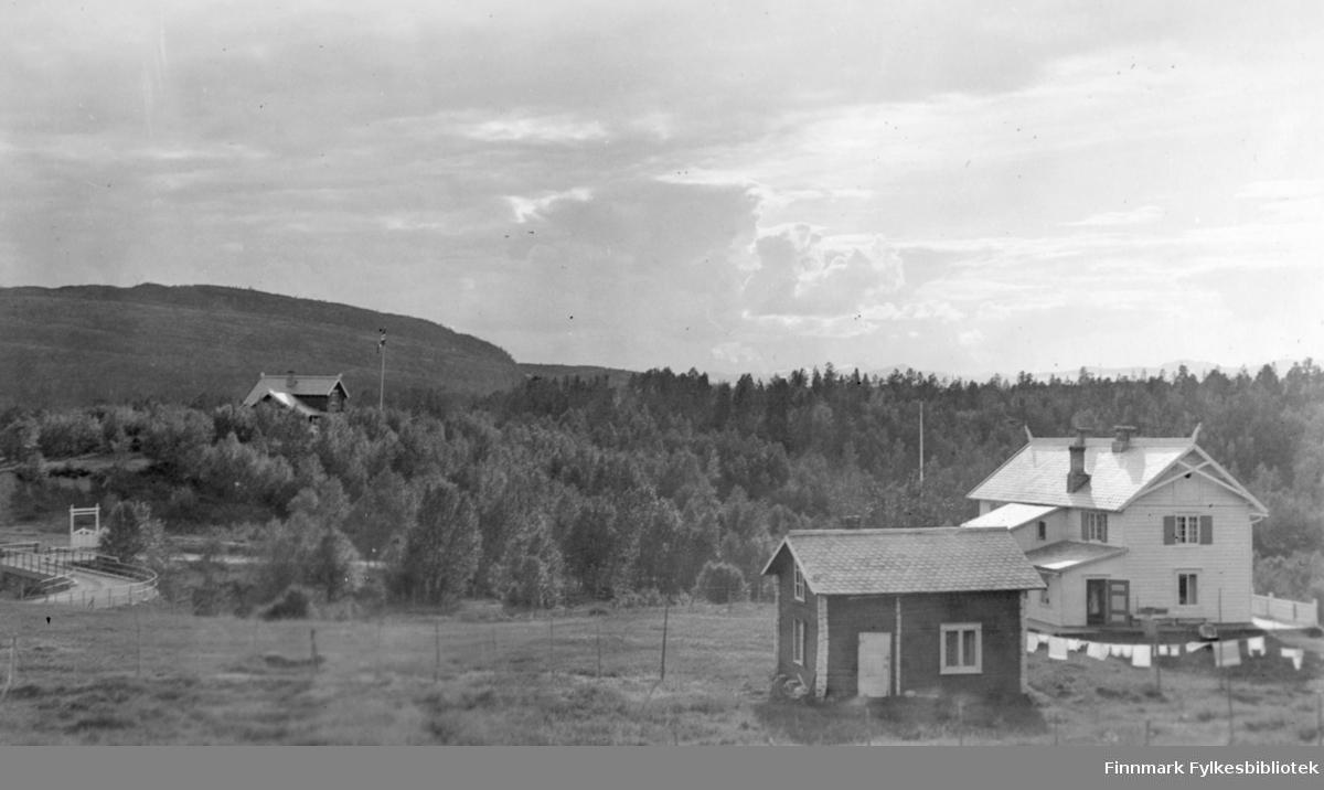Et stort, hvitt hus står på et jorde. Huset har et trappeformet tilbygg, skifertak og to piper. Foran det står et mindre bygg, også med skifertak. Klær henger til tørk på en snor fra det minste bygget og videre nedover. Litt av et gjerde står helt nede til høyre. Deler av området består av gress. I bakgrunnen er det skog og helt til venstre ses en liten bro. Toppen av en hus ses i skogen til venstre på bildet. Mye skyer på himmelen, men sola bryter igjennom og skinner på huset nærmest.