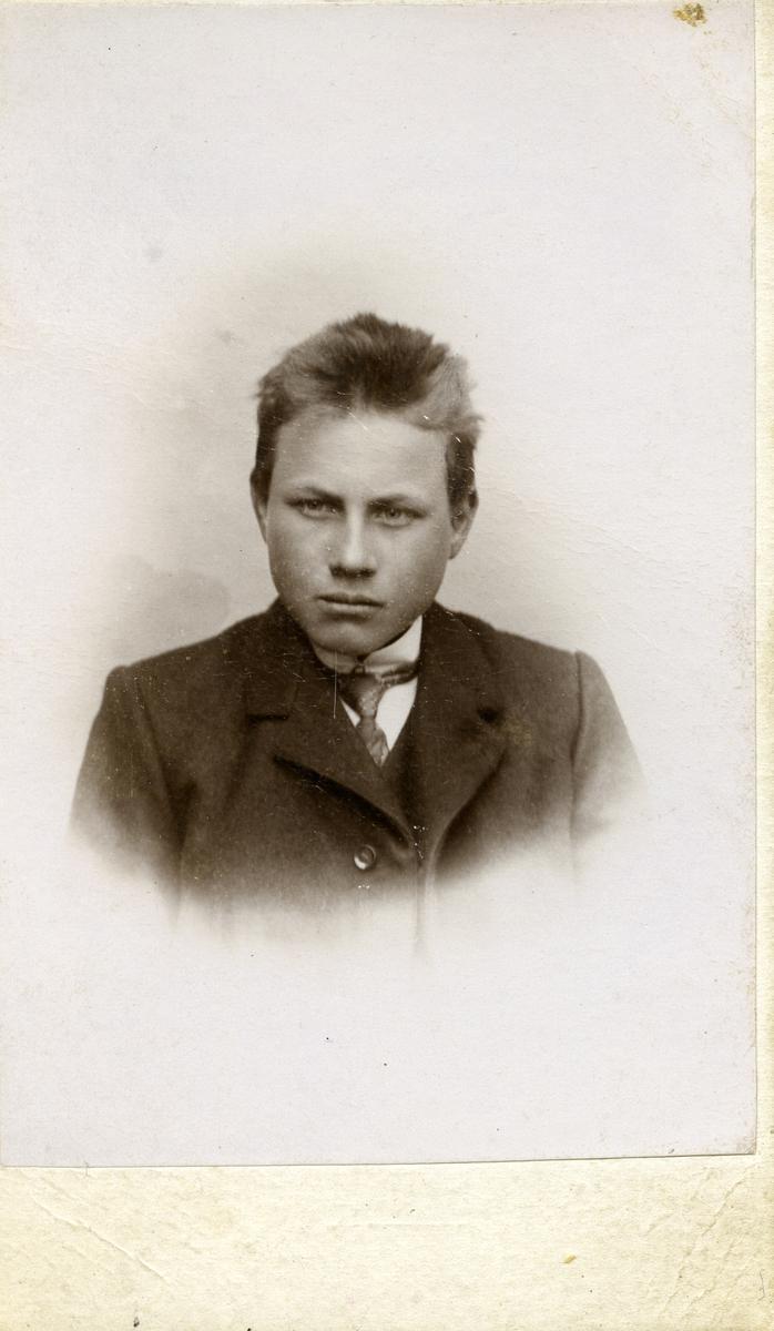 """Portrett av ung mann. Ikledd dress og slips. Tekst bakpå bildet er : """" Skytterkamerat til Gullik""""."""