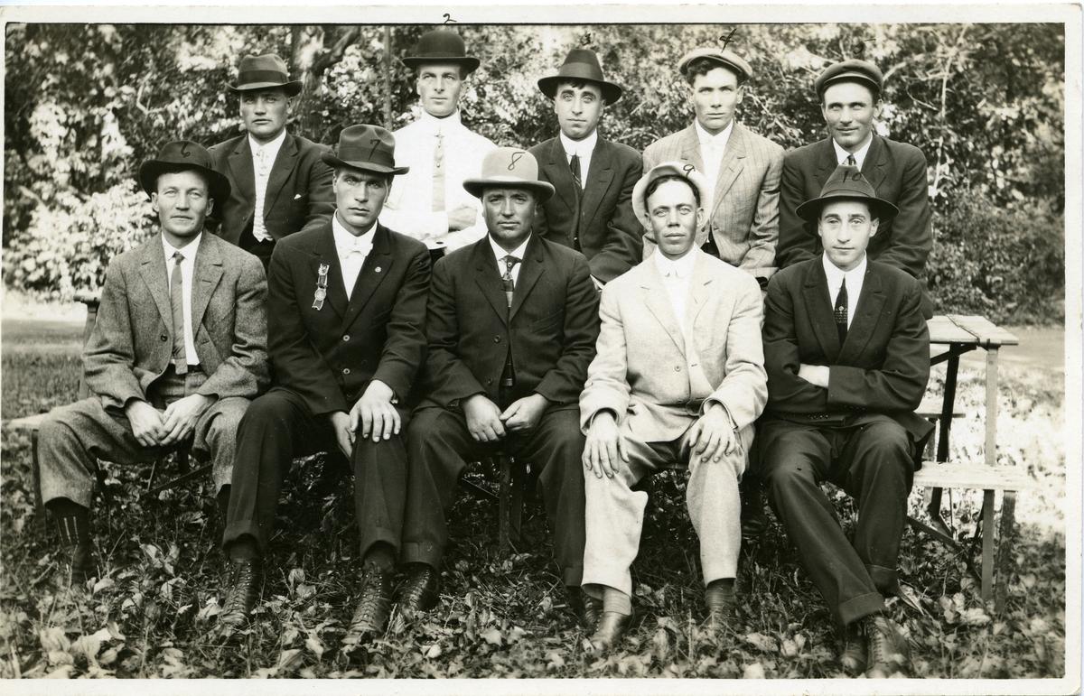 Gruppebilde av ti menn sittende på en benk. Alle kledd i dress og hatt.