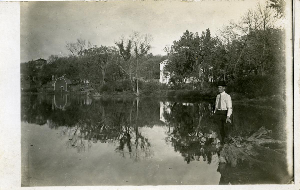 Mann stående på ei trerot i et vann/innsjø. Hus i bakgrunnen. Dette er et postkort 1911-1912