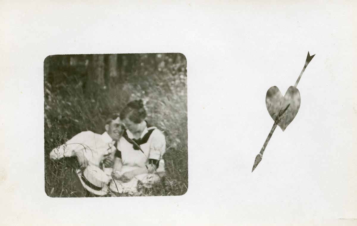 Postkort som viser to unge mennesker som sitter i gresset. Kortet har et hjertemotiv med en pil gjennom, til høyre for bildet.