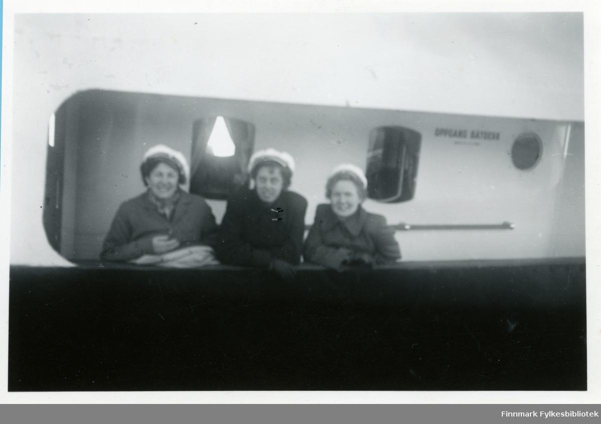 Medlemmer av Vadsø damekor ombord et skip, muligens hurtigruten. Damene har på seg hvite hatter (trolig kor uniform) og kåper. Bak kvinnene kan man se vindu. De lener seg mot båt gelenderet.