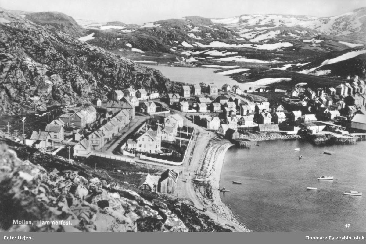 Et postkort med Hammerfest som motiv. 'Mollen, Hammerfest' er trykket på postkortet. På bilde kan man se flere hus og gater. Enkelte av husene har store hager. Langs fjæra kan man se robåter og kaier. Det er blitt satt opp strømlinjer rundt om kring. I bakgrunnen kan man se fjell.