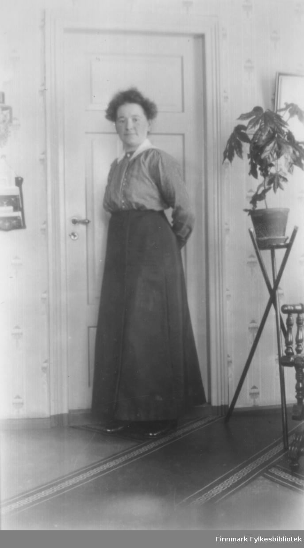 Fotografi av Anna Katrine Christensdatter, f.1885. fra eiendomen Djupdalen i Tverrelvdalen i Alta. Gift og bosatt i Karasjok med forretningsmannen Oscar Næss f. 1869. De fikk tre barn, Alfhild, Georg og Oscar. Hun var datter til Christen Arnesen og Elen Marie Kristensen f. Thomassen, og hun hadde mange søsken. En av dem, Karen Thomine Lovise Johansen, var flere ganger i Karasjok, og hjalp til i huset, på butikken og telefonsentralen som de hadde. For å komme til Karasjok gikk det tre dager over fjellet, ofte med kløvhest. Anna hadde eget fotoapparat, og tok mange bilder av familien, som hun fremkalte selv. På bildet ser vi henne posere inne, foran en dør. Hun er kledt i en bluse med hvit krage, og et langt mørkt skjørt. På bena har hun blanke svart sko. Det ligger løpere på gulvet. Til høyre står en pidestall med en grønnplante på. En del av en stol og et bilde på veggen ses litt av. Veggen har tapet med mønster