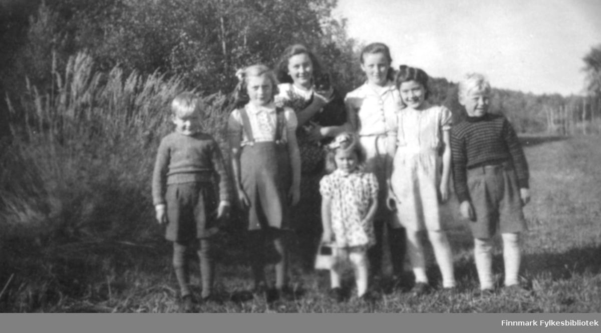 Syv barn og en katt. Fra venstre står: Johan Kristian Johansen, Anna Elisabeth Johansen g. Uglebakken, giver av bildene Karen Kristine Johansen g. Jakobsen, Ragnhild Marie Johansen g. Suhr, Kirsten Kristensen og Øystein Oppgård. Foran med håndveske står Åse Thomine Johansen g. Ingebrigtsen. Karen Kristin holder en svart katt. Det er skog i bakgrunnen av barna. Det er høye strå i skogkanten. Guttene har knebukser, og gensere på seg, mens jentene er kledt i kjoler, og skjørt