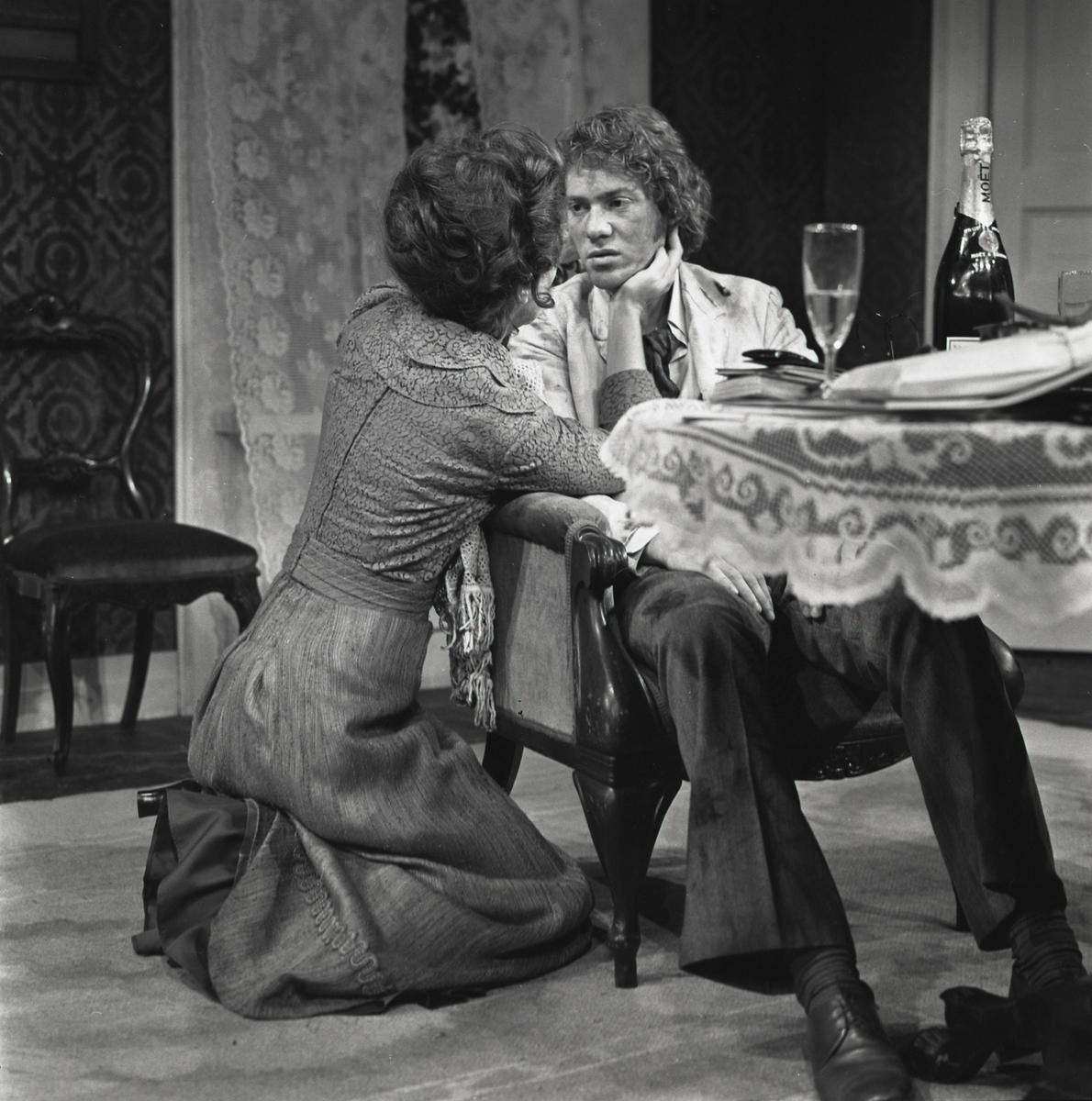 """Scene fra Nathionaltheatrets oppsetning av Henrik Ibsens """"Gengangere"""". Fru Alving sitter på kne og holder Oswalds ansikt i hendene. Oswals sitter i en lenestol ved et bord. På bordet står en flaske sjampanje og flere bøker. Forestillingen hadde premiere 4. oktober 1972. Pål Løkkeberg hadde regi og medvirkende var Helen Brinchmann som fru Alving, Frøydis Armand som Regine Engstrand, Svein Sturla Hungnes som Osvald, Frank robert som Pastor Manders og Rolf Søder som Snekker Engstrand. .."""