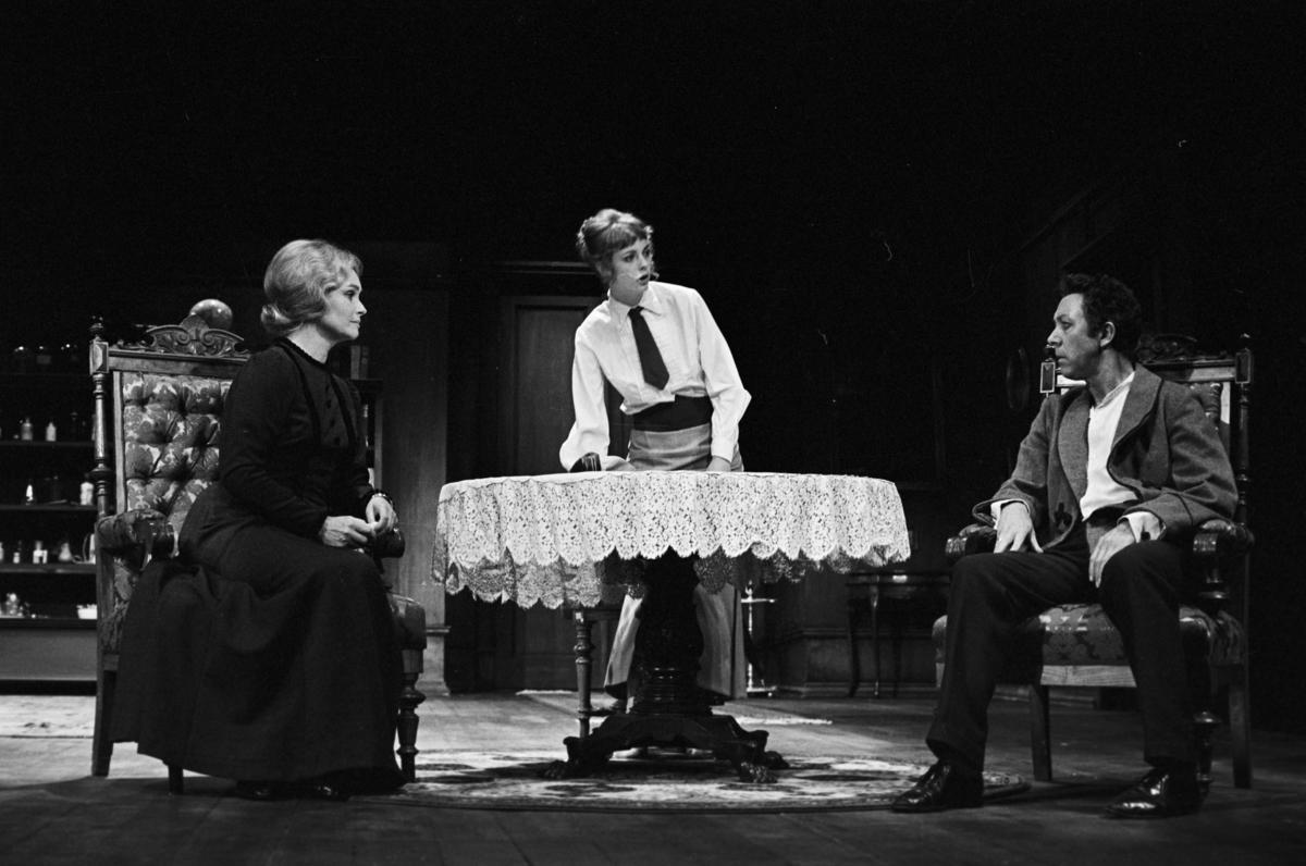 """Scene fra Nationaltheaterets oppsetning av Henrik Ibsens """"En folkefiende"""". Forestillingen hadde premiere 27. september 1979. Charles Marowitz hadde regi, og medvirkende var blant annet Per Theodor Haugen som Dr. Thomas Stockmann, Ingerid Vardund som Fru Stockmann og Tor Stokke som Peter Stockmann."""