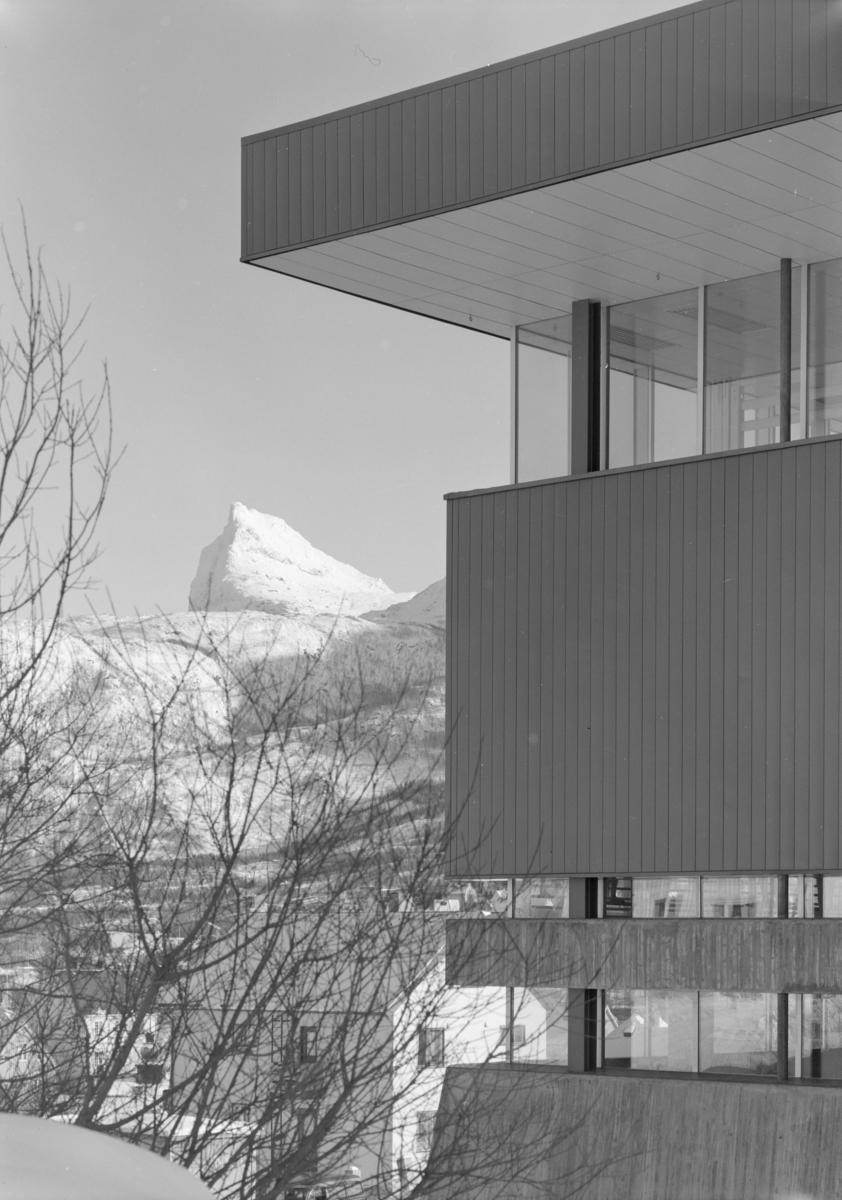 Arkitekturfoto av Idrettens hus i Narvik. I bakgrunnen sees en snødekket fjelltopp.