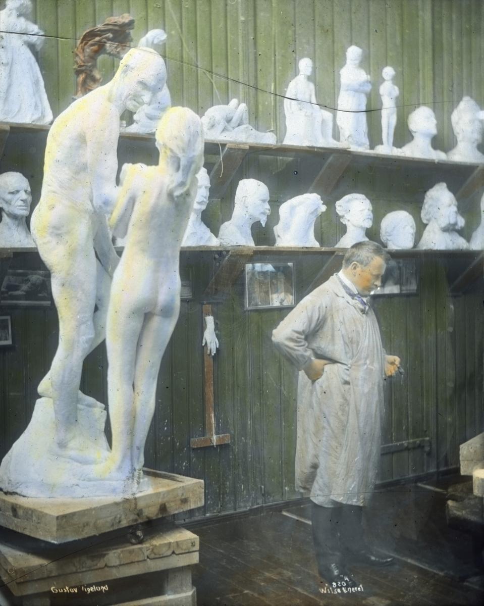 Håndkolorert dias. Portrett av billedhuggeren Gustav Vigeland i hans atelier. Bak Vigeland står en rekke skulpturmodeller og byster. I forgrunnen står en skulpturgruppe av en eldre mann og en yngre jente.