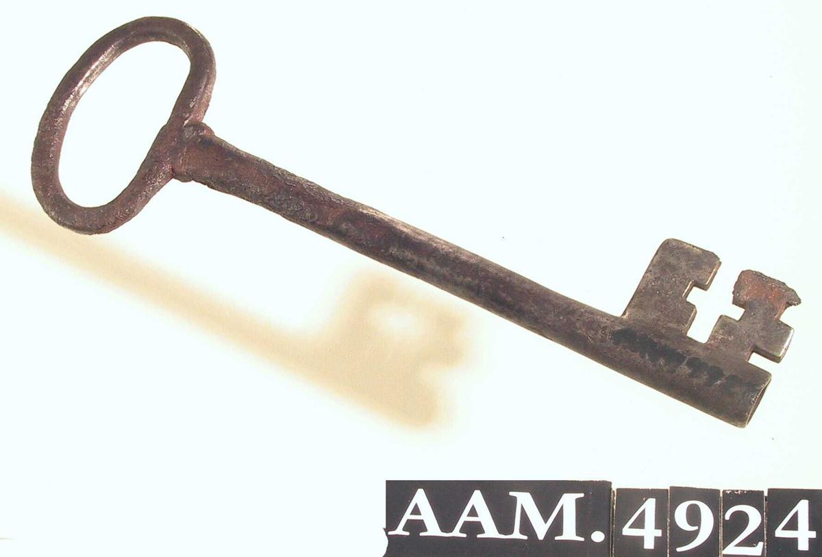 Nøkkel,  ant. til hoveddør. Jern.  Rett, hul pipe, ovalt håndtak, plate med korsformet åpning.  Innk. 28/5 1965, lå på bunnen av døpefont Eide, AAM.4909.
