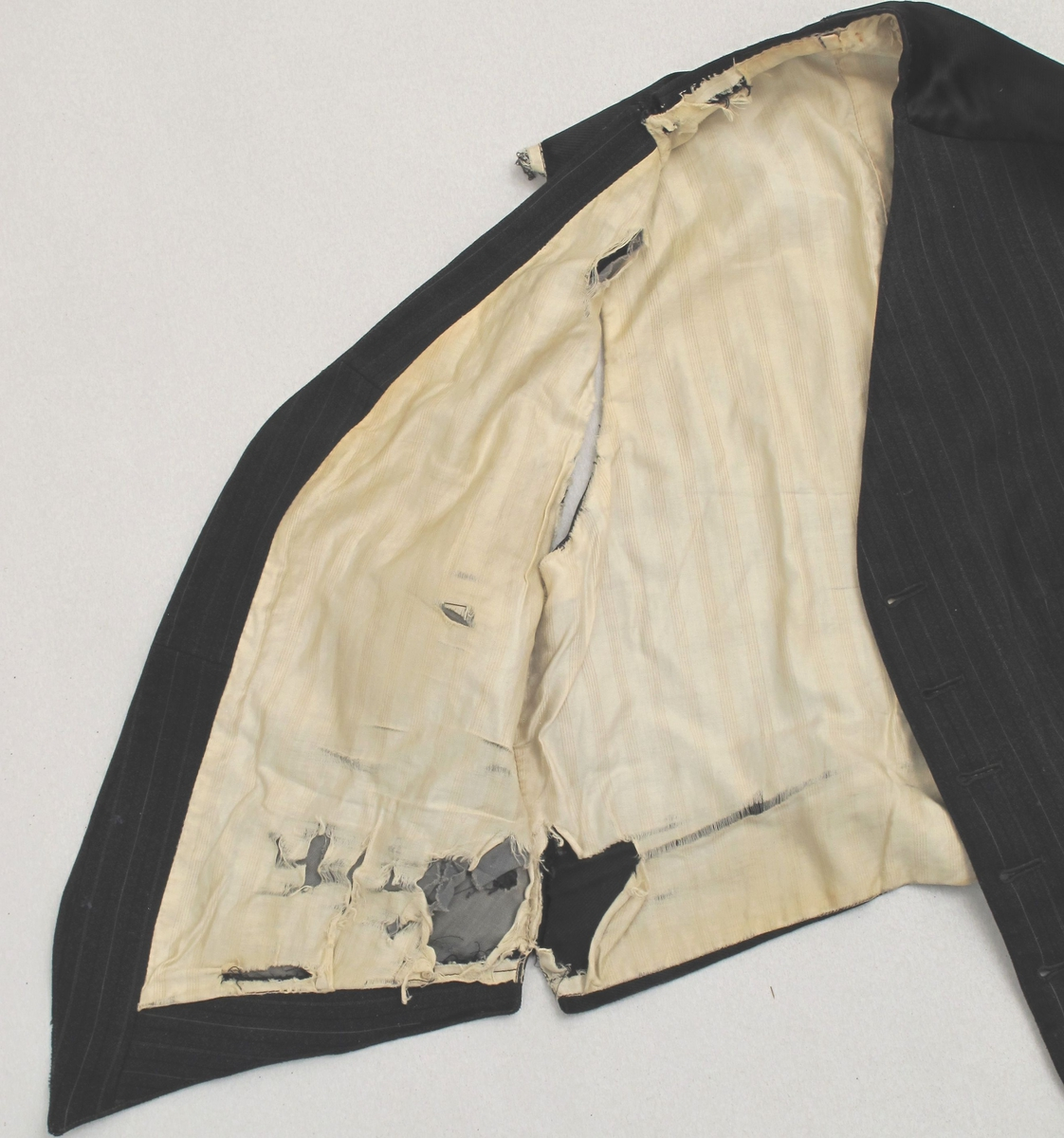 Herrevest i koksgrått stripet ullstoff.  Fire lommer, seks knapper. Ryggstykke av sort silke. Lyst for. Spenne i ryggen.