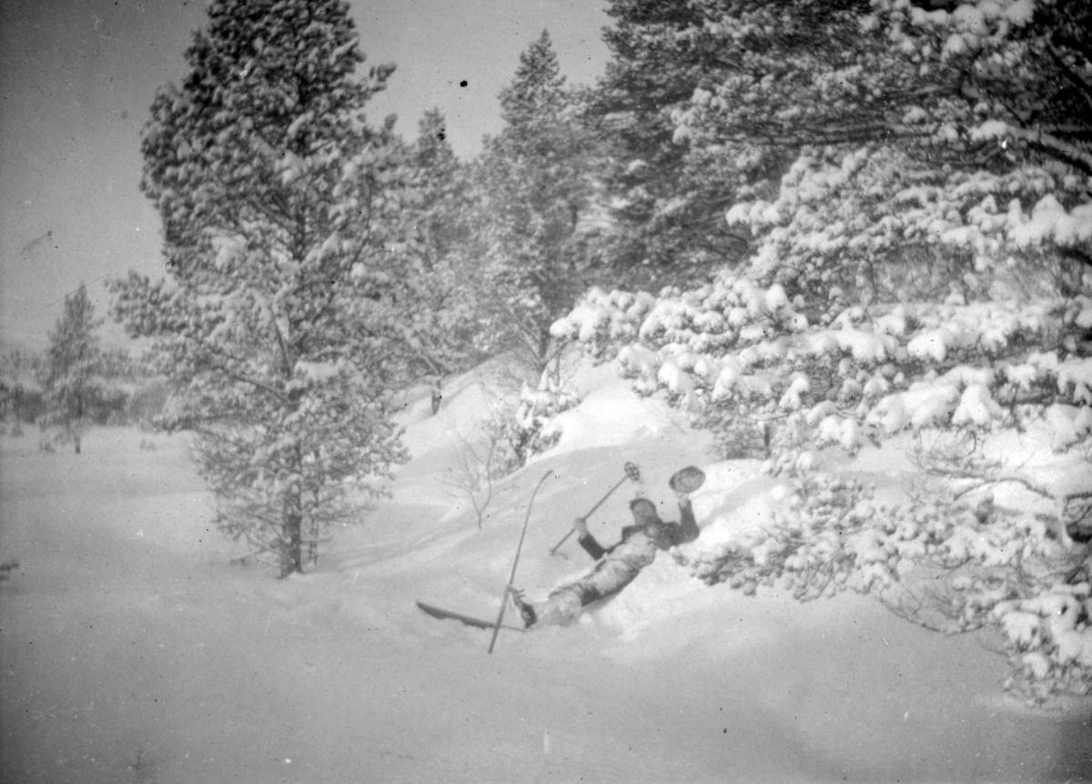 Johannes Büll-Hansen ligger i snøen og ser ut som om han har falt. Han har ski på bena, en stav i hånden, og er kledd i vinterklær. Han er omringet av skog.