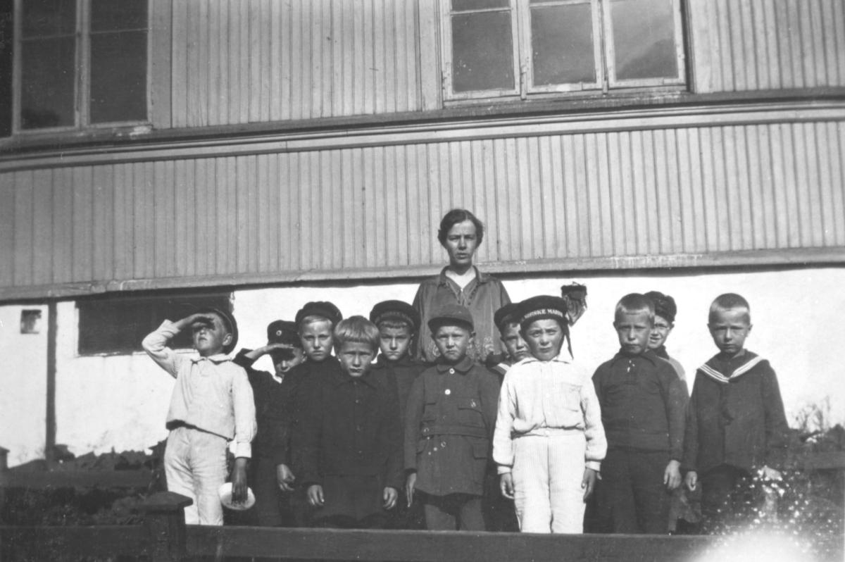 """""""Fra lærerskolen. Frøken Hernes (?). Tromsø."""" En gruppe gutter står foran en kvinne. Enkelte har på seg uniform, og lue."""