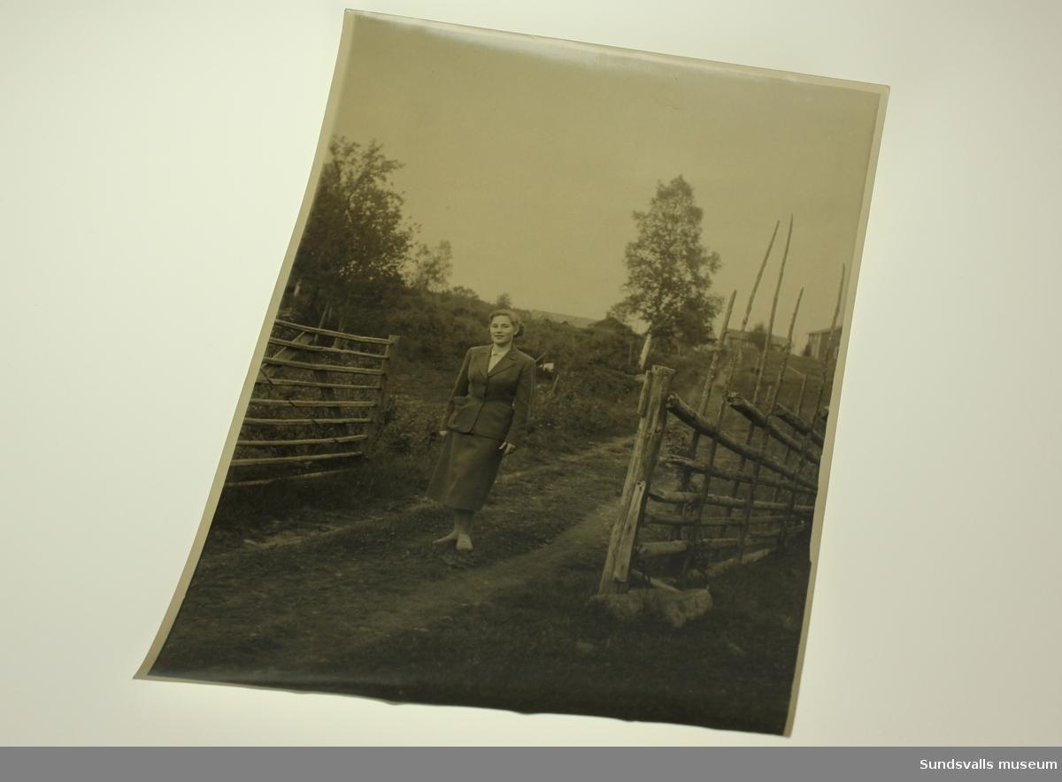 En kvinna i dräkt placerad i ett grindhål strax nedan ett hemman bestånden av tre byggnader.