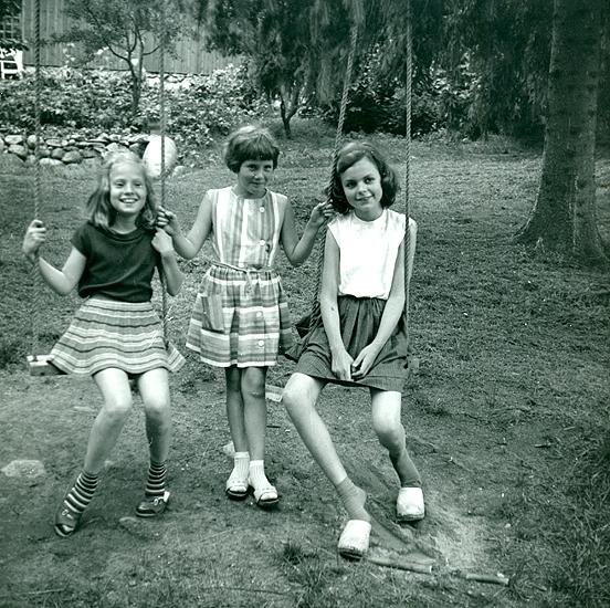 """Sommaren 1962 hos Agneta Turesson. Veronika i mörkröd topp med båtringning och hemmastickad grå yllekjol med ränder i rött, gult, vitt Agneta T. i mitten min """"bästis"""" i flera år. Elisabeth Madgård i diadem och vit blus, blå kjol med sparveck (skulle släppts ner) och träskor.  (Fotograf kan vara Gertrud.)"""