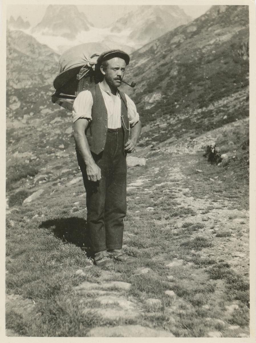 Mann med ryggsekk på fjelltur i Grønlandske fjell.