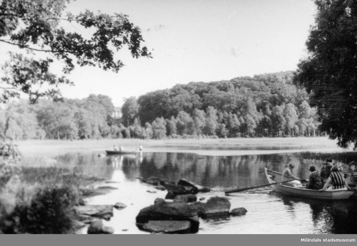 Vy över Stensjön, 1920-30-tal. Personer som ror ekor och en person som står i vattnet. I bakgrunden skymtas Gunnebo slott.