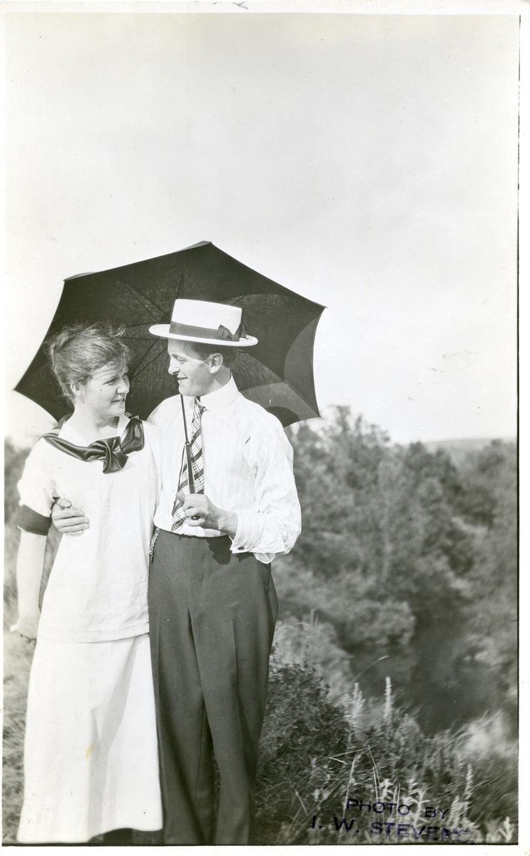 Portrett av to personer. Personene er Ingvald Brekken med en dame. Kvinnen er iført hvit kjole og mannen er iført skjorte og slips. I tillegg er han iført en hatt mens han holder en paraply.