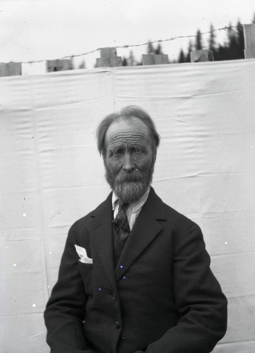 Mann avbildet  i halvfigur, sittende foran et laken som er stiftet opp på et tregjerde med piggtråd på toppen.