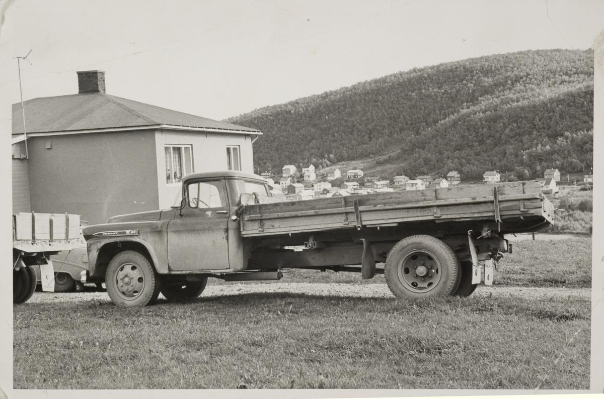 Lastebil på øversiden av hus på Tofta. Skogveien i bakgrunnen.