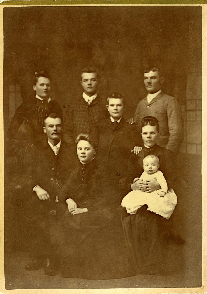 En gruppe med mennesker er avbildet på dette fotoet. Bildet fremstiller sannsynlig et familieportrett. Babyen på bildet er iført en hvit kjole så det kan kanskje være snakk om et dåpsbilde.