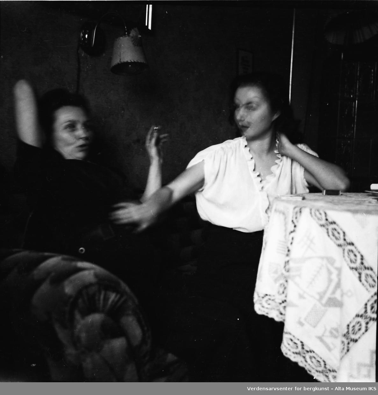 To kvinner sitter i en sofa og røyker sigaretter. Kvinnen i hvitt har en hånd på magen til kvinnen med sigaretten i hånden.