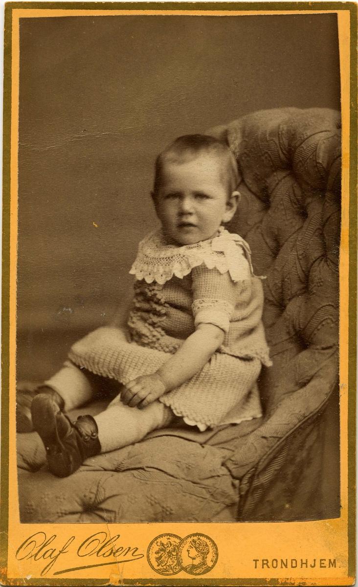 Et lite barn sitter på en stol.