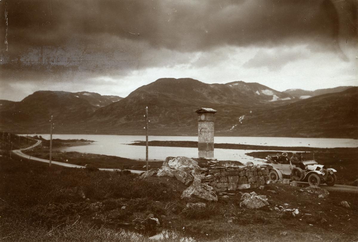 En bil med passasjerer passerer den gamle fylkesstøtten ved Filefjell. Smeddalsvatnet i bakgrunnen.