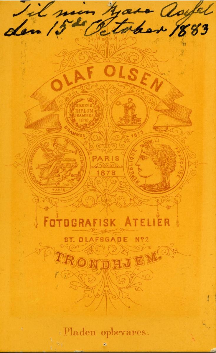 """Påskrift bak bildet: """"Til min kjære Axsel den 15 Oktober 1883. Fra Bestemor Kjelland."""" Portrett av bestemor til Axel Borthen, Gabrielle Mathea Kirstine Kielland. """"Axsel"""" det refereres til er trolig Axel Borthen, født 1869 i Vardø. Axel Borthen er i 1885 registrert i Kristiansund, Møre og Romsdal, som tilreisende. Han er samtidig registrert i folktelling for Vardø i 1885 som """"bortreist og fotograflæring"""". Det kan antas at han er bortreist for å lære fotografyrket i Kristiansund.   Axel Borthen er sønn av """"Kjøbmand, Dampskibsexpeditør, Producent af Fisk og Tran"""" Henrik Marthin Borthen og Anna Charlotte Cathrine Borthen, født Kielland i 1837). Det er altså bestemor på morssiden som kommer av Kielland-slekten. I 1910 er han gift med Sigrid Borthen, født 24.11.1875 i Sydvaranger. De har adresse Karpbugt, Sørvaranger.  Bestemor Kielland er Mathea Christine Kielland, født 26.oktober 1817 i Oslo. Giftet seg med Gabriel Kirsebom Kielland, født 2.juni 1805, i Stavanger. De hadde 7 barn, Arne Kielland Borthen, Harald Knoff BOrthen, Anna Mathea Borthen, Axel Borthen, Sverre Borthen, Olaf Borthen og Ingvald Borthen.  Notater funnet om Gabriel Kirsebom Kielland: """"Var noen tid på kontoret hos byfogden i Stavanger og derefter hos sorenskriveren i Søndhordland. I 1828 kom han til Christiania og tok 1830 (1831?) norsk juridisk eksamen, hvorefter han ansattes i finansdepartementet.I november 1835 blev han sendt til Trondhjem for å ordne affærene ved skattefogedkontoret, og fungerte derefter i 11 år som skattefoged. Var 1847 - 48 kst. politimester i Trondhjem. I november 1842 ble han revisor ved Norges Banks hovedkontor i Trondhjem, og overtok 1. mars 1849 posten som bankens kasserer, hvilken stilling han innehadde til sin død. Han var i en årrekke inntil 31. desember 1880 direktør i Trondhjems Sparebank, og vedble deretter inntil sin død å stå som en av bankens 50 forstandere. Han eiet gården Kongens gt. 66 i Trondhjem og kjøpte 1851 en liten eiendom """"Fridarheim"""" i Steenbjerget, som h"""