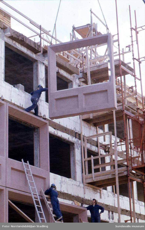 Nordvästra hörnet av kvarteret Olympen får ny fasad. Stora betongsektioner lyfts på plats med kran.