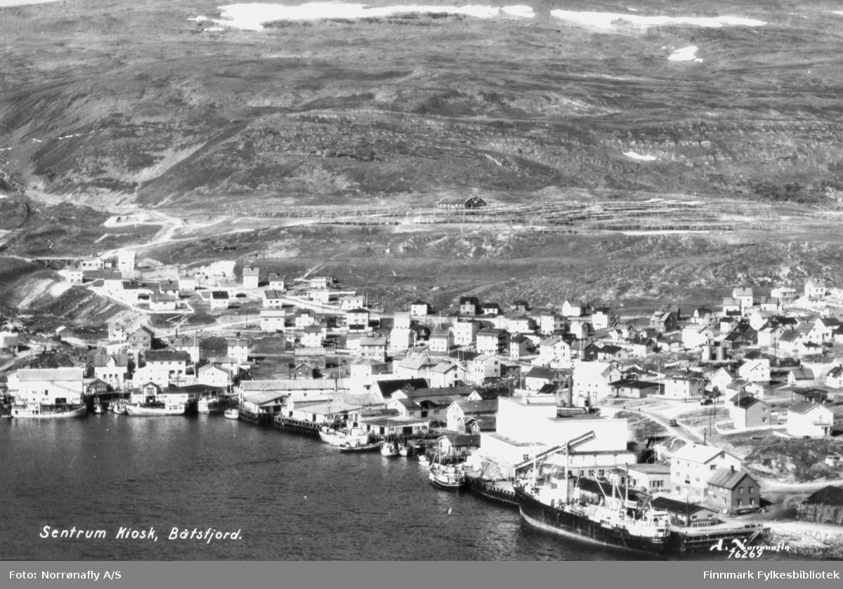 """Oversiktsbilde av Båtsfjord. Påskrift på bildet: """"Sentrum Kiosk, Båtsfjord"""".  Helt til høyre ved kaia ligger Vesterålskes godsbåt """"Senja"""". Bildet er trolig tatt i siste del av 1900-tallet. (1950?)"""